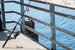 Fishing Pole. Close up of a recreational fishing pole with its reel and lure on a fishing pier royalty free stock photos