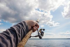 Fishing pole in hand on a background of a cloudy sky. Horizon is far away Royalty Free Stock Image