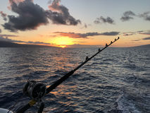 Fishing pole in the ocean waters at sunset. One last round of fishing as sun sets off coast of Maui, Hawaii Royalty Free Stock Photo
