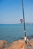 Fishing pole with red reel on blue sea Stock Photography