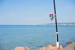 Fishing pole with red reel on blue sea Stock Photo