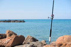 Fishing pole with red reel on blue sea Royalty Free Stock Photo
