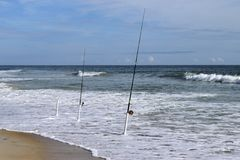 Fishing poles on beach Stock Photography