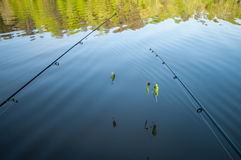 Fishing poles over still lake Royalty Free Stock Photo