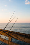 Fishing Poles on Pier with Clouds Royalty Free Stock Photo