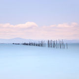 Fishing poles and soft water on sea landscape. Long exposure. Stock Images