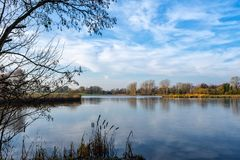 Fishing pond in Cheshire UK. Peaceful fishing pond or lake on a early morning in autumn in the Cheshire countryside England United Kingdom royalty free stock photo