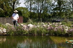 Fishing at the pond. He holds a fishing rod in his hand Stock Photo
