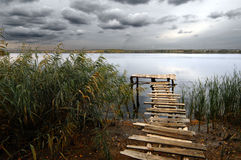 Fishing pond under stormy clouds Stock Images