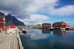 Fishing port in Henningsvaer. Picturesque fishing port in town of Henningsvaer on Lofoten islands in Norway with typical red wooden buildings and small fishing stock image