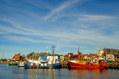 Fishing port of Ustka with old lighthouse. And blue sky stock images