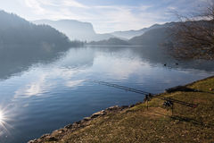 Fishing in pure lake bled in slovenia. Fishing rods on beautiful lake bled surrounded by julian alps in winter season in back light sunny blue sky, bled Stock Image