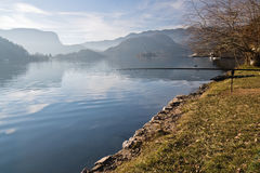 Fishing in pure lake bled in slovenia. Fishing rods on beautiful lake bled surrounded by julian alps in winter season in back light sunny blue sky, bled Stock Photography