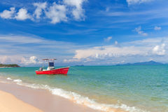 Fishing red boat on anchor near sand beach Royalty Free Stock Photo