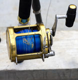 Fishing reel. Black and Gold game fishing reel in a rod holder Royalty Free Stock Images