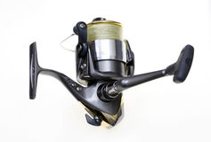 Fishing reel. Sports fishing reel loaded with yellow braid line on white Stock Photography