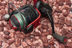 Fishing reel on the beach with small red stones Royalty Free Stock Photo