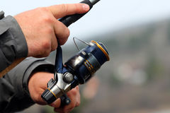 Fishing Reel. Closeup of a boys hand holding a fishing rod and reel Royalty Free Stock Photography