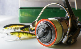 Fishing reel and fishing bait on the background of the box with lures Royalty Free Stock Photography