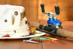 Fishing reel with hat and color lures royalty free stock photos