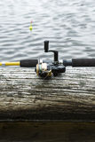 Fishing reel on Log in Lake Stock Image