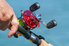 Fishing reel. Red fishing reel with man's hand Royalty Free Stock Images
