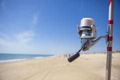 Fishing reel on rod detail with angling fishers at bottom on the. Sea, Huelva, Spain Royalty Free Stock Photography