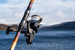 Fishing reel and rod with sea, sky and mountains Stock Image