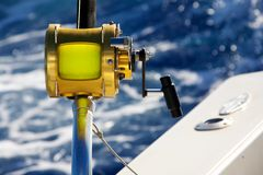 A fishing reel set against blue ocean stock images