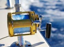 A fishing reel set against blue ocean Royalty Free Stock Image