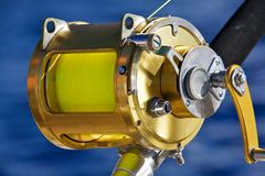 A fishing reel set against blue ocean Royalty Free Stock Photo