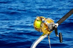 A fishing reel set against blue ocean Stock Photos