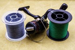 Fishing reel and spools of cords on the background of tarpaulin. Green and gray fishing line. Spools of braided fishing line. S royalty free stock photo