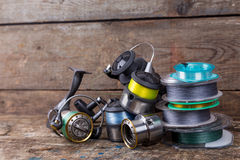 Fishing reels and spoole with line on wooden background royalty free stock photos