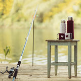 Fishing on the river. Fishing rod and a thermos Cup in a knitted Royalty Free Stock Photos