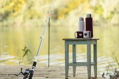Fishing on the river. Fishing rod and a thermos Cup in a knitted Royalty Free Stock Image