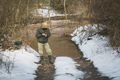 Fishing on the river in the winter. Fisherman install the hook stock images