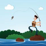 Fishing in the river. Young man happily caught a fish while fishing in the river Stock Image