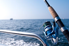 Fishing road on boat at sea. Closeup of fishing rod and reel on side of boat with blue sea in background and copy space royalty free stock photos