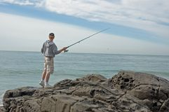 Fishing from a rock. Man fishing from a rock stock images