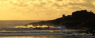 Fishing rocks golden sunrise Stock Image