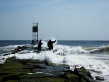 Fishing on the Rocks. Two fisherman fishing on the Indian river and inlet wave barrier Royalty Free Stock Photos