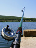 Fishing rod. Rod for fishing with the reel on the background of the lake and green forests Royalty Free Stock Photography