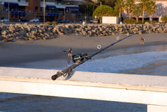 Fishing Rod. Inserted iin holder on pier railing Stock Image