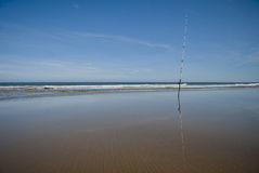Fishing rod at the sand of the beach. Fishing rod on the beach Stock Image