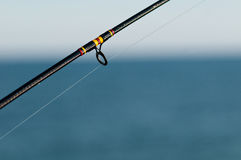 Fishing rod. Over a blurred water horizon with selective focus Royalty Free Stock Images