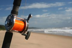 Fishing rod. With bright colored line planted on the beach Royalty Free Stock Images