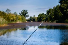 Fishing rod against blurred canal stock image