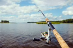 Fishing rod on the background of a blurred islet of green grass. Focus on the fishing reel Stock Photography