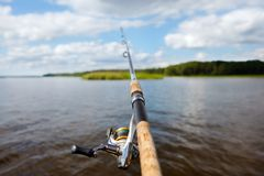 Fishing rod on the background of a blurred islet of green grass. Focus on the fishing reel Royalty Free Stock Photography